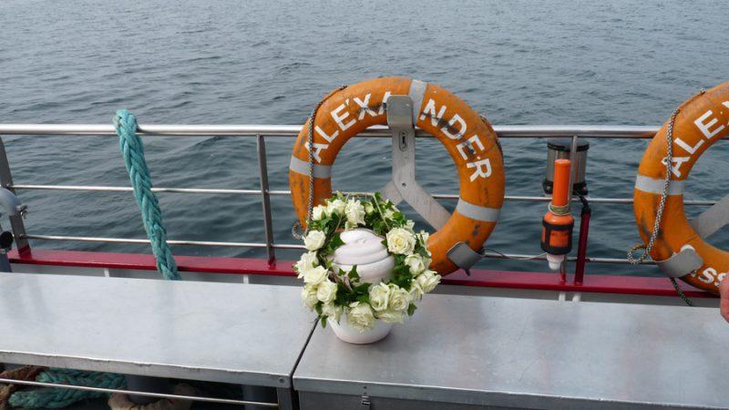 Bestattungsurne von Seebestattung Rügen mit weißen Blumen am Board der MS Alexander